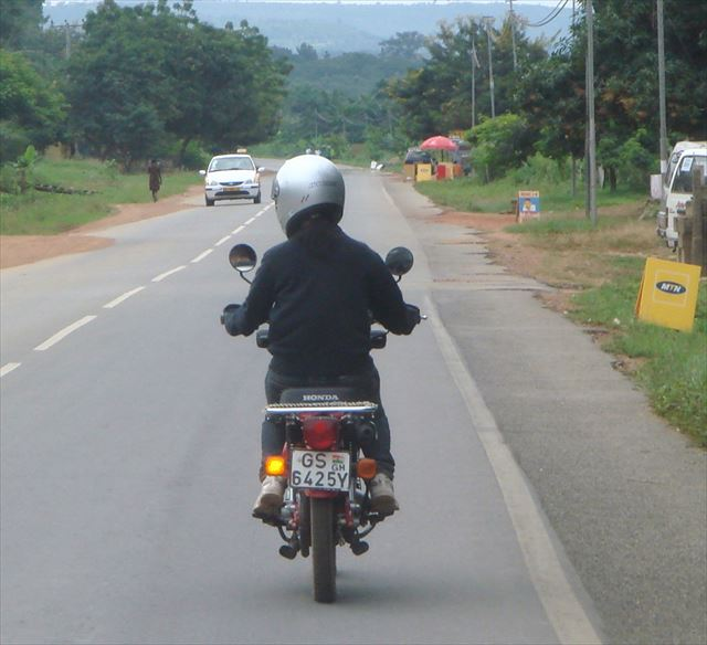 任地ガーナにてバイクに乗って担当先の村へ走る後町さん