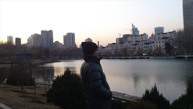 冬の大連にて河川を望む田辺さん