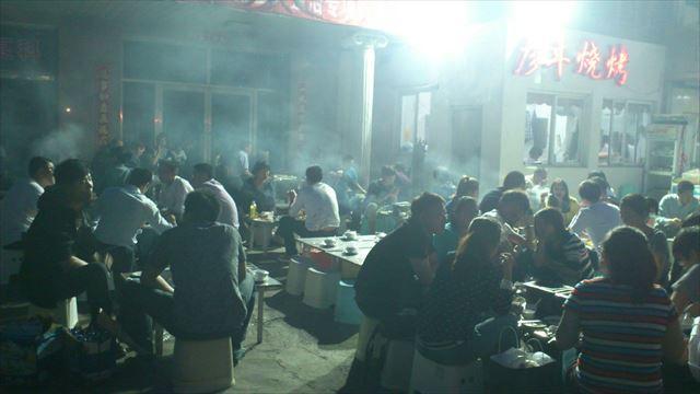 野外の羊肉串店にて、煙が立ち込める。