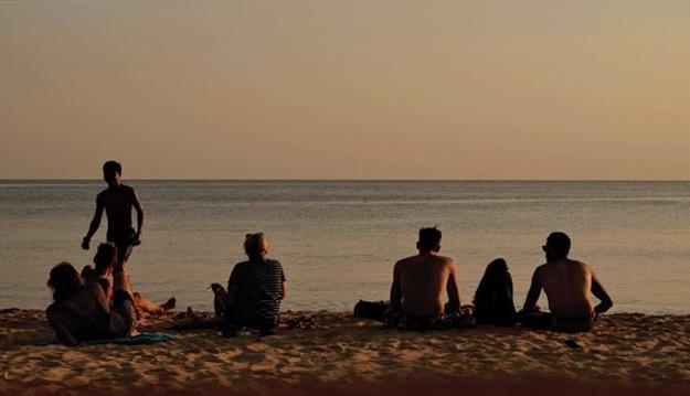 ケップのビーチから望む夕日と、人々の後ろ姿。