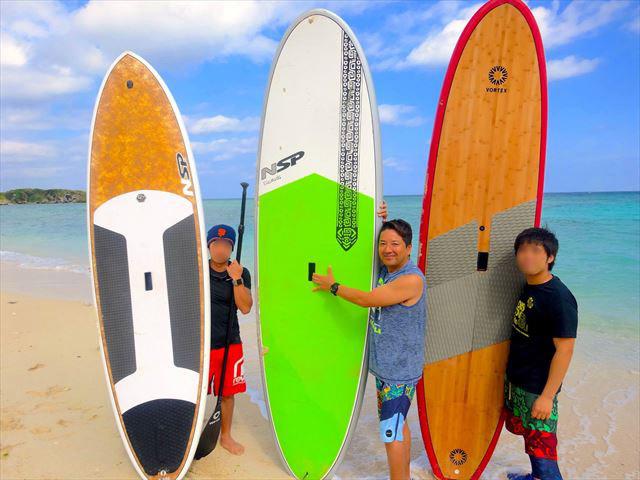 沖永良部島の青い海をバックに、サップを持つ金城さんと二人の参加者。