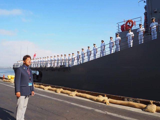 海上自衛隊関連の仕事にて、スーツ姿で船を望む金城さん。