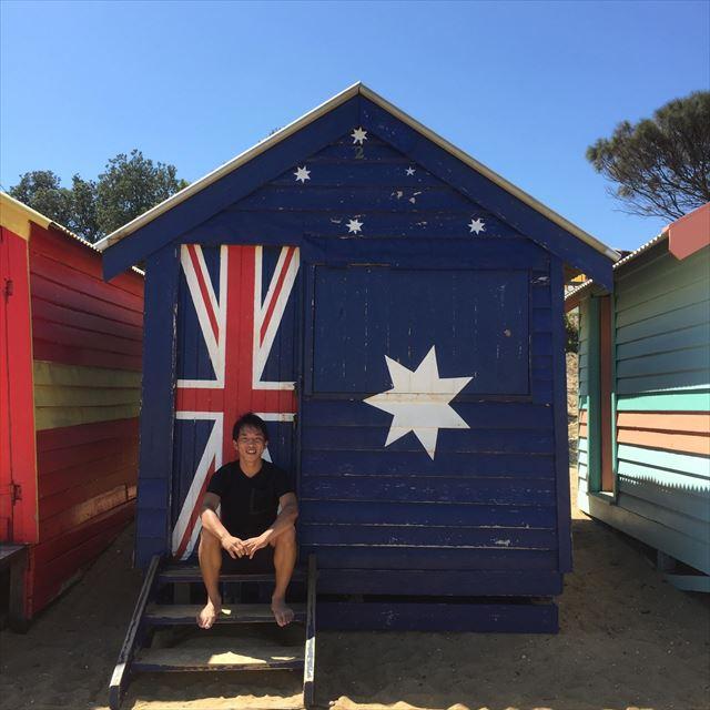 オーストラリア国旗柄の小屋の前に座る関谷さん