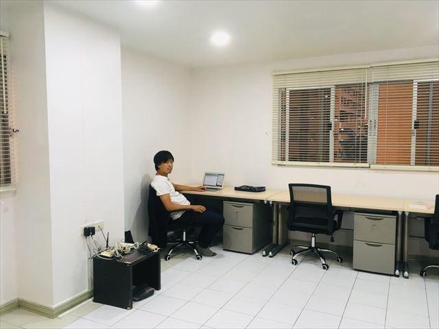 SWIMオフィスでデスクに座る後潟さん