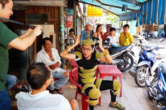ベトナムでドリアンの皮を身にまとう私をそれを笑顔で囲む地元の人たち