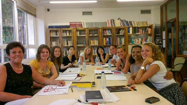 マラガの語学学校にて、テーブルに座って学ぶ10人の集合写真。
